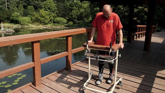 Darek Fidyka walks with the aid of leg-braces and a walking frame