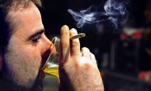 A man drinks beer while smoking a cigarette at the Goiritxu bar in Guernica December 25, 2010. A tough new law expected to pass the Spanish Senate on January 2, 2011 will prohibit smoking in bars as well as playgrounds, schools and hospitals. REUTERS/Vincent West (SPAIN - Tags: SOCIETY)